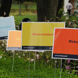 Four signs expressing Welcome in various languages.