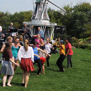 Members of the band Grupo Aye performing with people dancing in the grass in front of the band with a windmill behind the band.