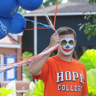A male college student with his face painted like a clown carrying a large bunch of blue balloons.