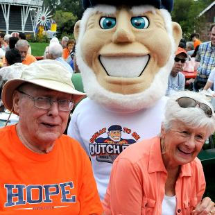 Dutch the mascot standing behind two adults seated at a picnic table.