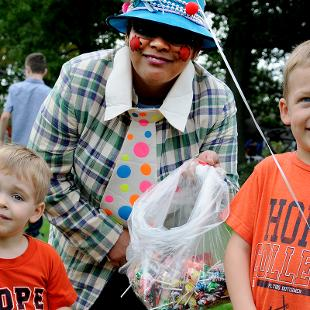 A clown with candy with two boys wearing Hope College shirts.