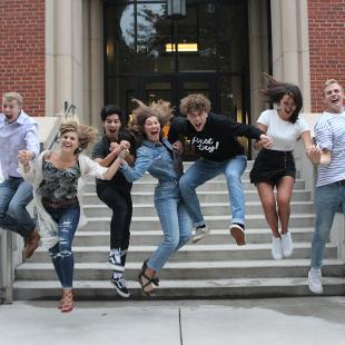 Worship Team Y jumping in front of the Bultman Student Center
