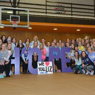 Forty-four women pose for a photo during the Relay for Life campus event in the Dow Center gym.