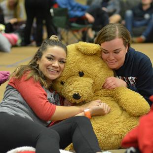 Two feel students pose with a large teddy bear.