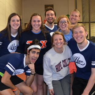 Four women and four men pose for a photo on the Dow Center indoor track during the Relay for Life campus event.