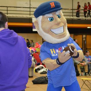 Mascot Dutch holds a football in the Dow Center gym during the Relay for Life campus event.