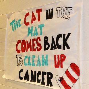 "Poster on the wall that says ""The Cat in the Hat Comes Back to Clean Up Cancer."""