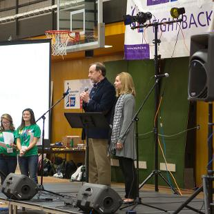 President John Knapp and Kelly Knapp on a stage addressing Relay for Life partipants in the Dow Center gym.