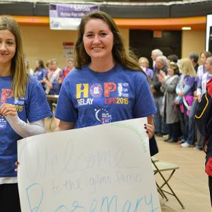 """Two female students with with sign that reads """"Welcome to Gilmore Famo Rosymary""""."""