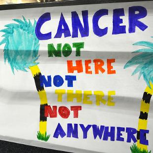 "Sign hung on walking track that says ""Cancer not here, not there, not anywhere.:"
