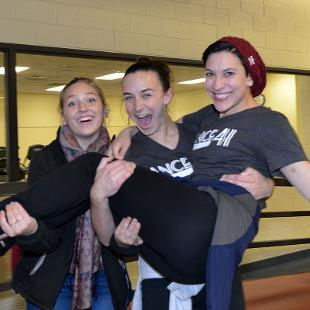 Three women walking on the Dow Center indoor track pose for a photo during the Relay for Life campus event.