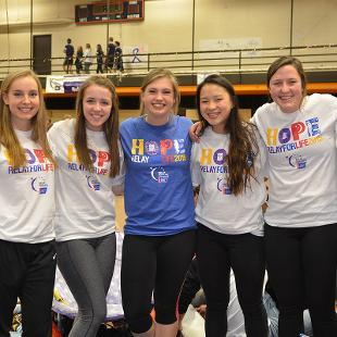Seven females  pose for a photo during the Relay for Life campus event in the Dow Center gym.