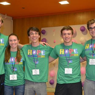 Four males and one female pose for a photo during the Relay for Life campus event in the Dow Center gym.