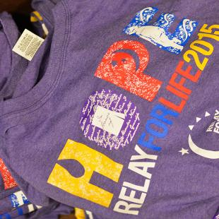 "Purple ""Hope Relay for Life 2015"" t-shirts on a table."