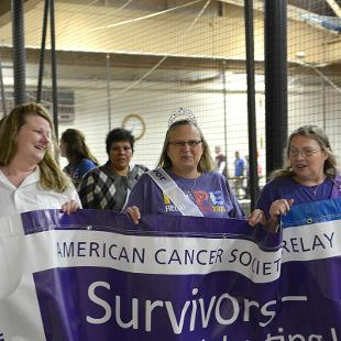 Students and cancer survivors walk on the Dow Center track during the Relay for Life event.
