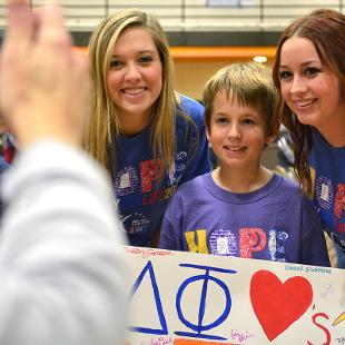 Two females pose with a young boy  for a photo during Relay for Life campus event the Dow Center gym.