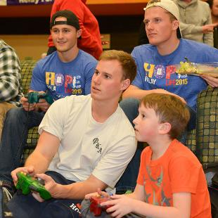 Five males play video games during the Relay for Life campus event.
