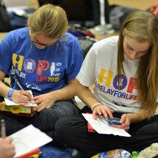 Two female students decorate luminaria bags.