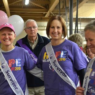"Three females wearing ""Cancer Survivor"" sashes walk around the track of the Dow Center."
