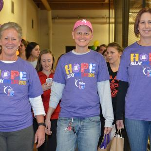 Three women walk on the Dow Center indoor track during the Relay for Life campus event.