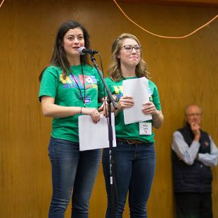 Two female student leaders address Relay for Life participants in the Dow Center gym.
