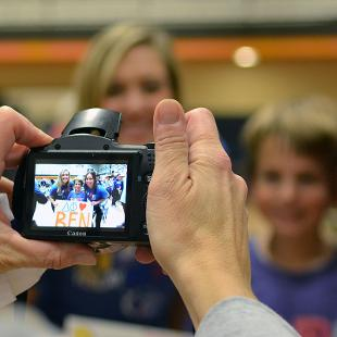 Photo of two hands and a camera taking a photo of females pose with a young boy  for a photo during Relay for Life campus event the Dow Center gym.