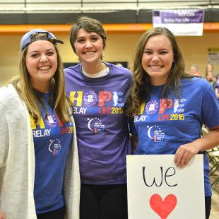 Three females posing for a photo during Relay for Life campus event the Dow Center gym.