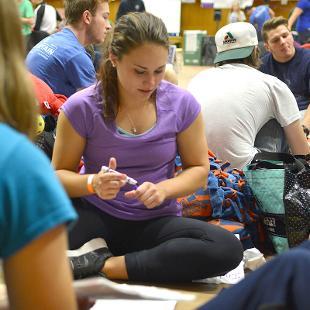 A female student decorates a luminaria bag.