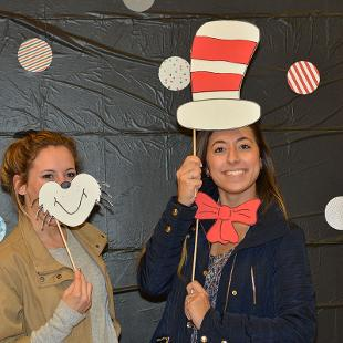 "Two women holding ""Cat in the Hat""  props pose for a photo during the Relay for Life campus event."