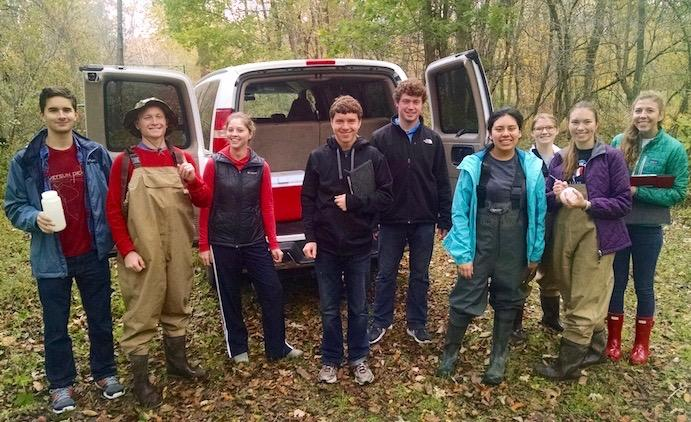Watershed group standing by a van