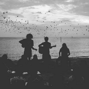 Group worship on the beach with a flock of birds flying by