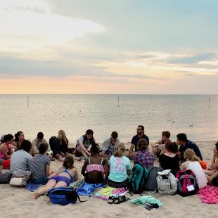 A group sitting on the beach at dusk