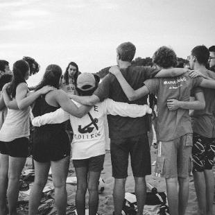 A group embraces one another in a circle on the beach