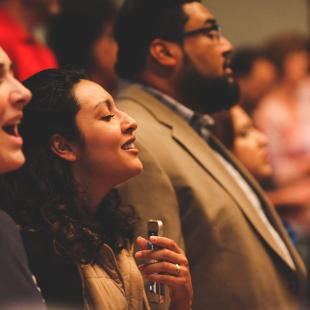 A group worshiping and singing with their eyes closed