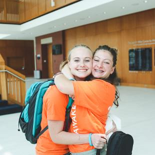 Two female students embrace one another in Jack H. Miller Center