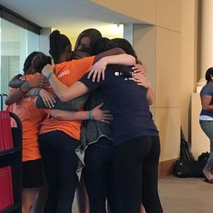 A group of students huddled together in a group hug
