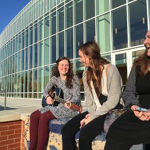 Three female students laughing outside the Jack H. Miller Center
