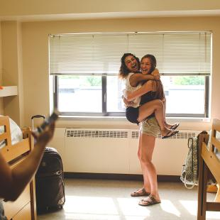 Two female students embrace one another in a dorm