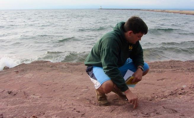 Student looking at rocks by the water