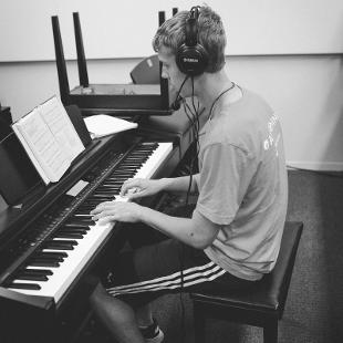 A male student practicing piano