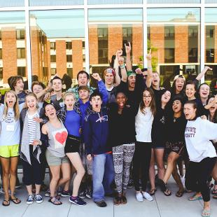 Awakening students taking a happy picture in front of the Jack H. Miller Center