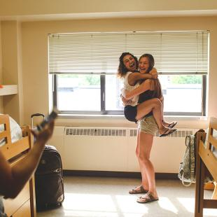 Two female students embracing one another in a dorm room
