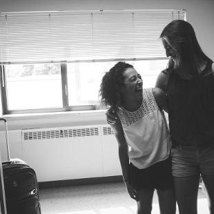 Two female students laughing with one another in a dorm room