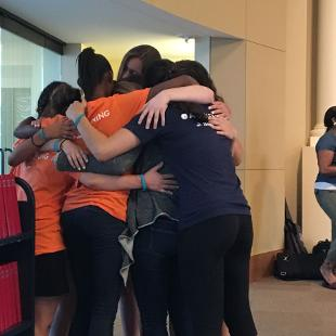 A group of students embrace one another in a group hug