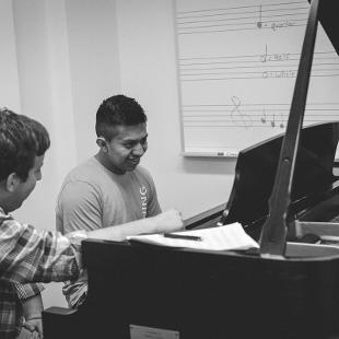 An Awakening intern assists a male student practice piano