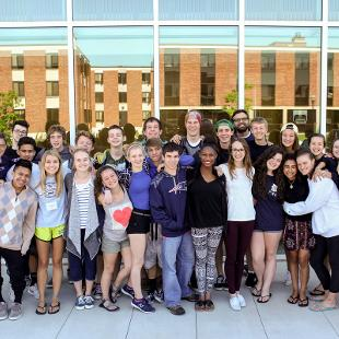 Awakening students smile for a picture in front of the Jack H. Miller Center