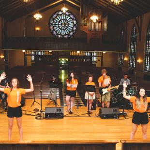 A worship band and student worship dancers lead a service in Dimnent chapel