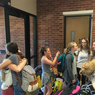 A group of students embrace in Phelps Hall