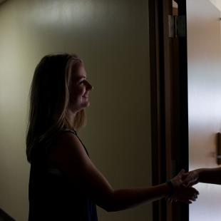 Two female students meeting one another in a dorm room