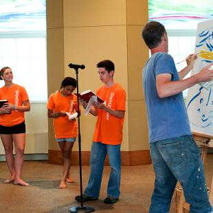 A group of Awakening students reading from the Bible while a man paints pictures behind them